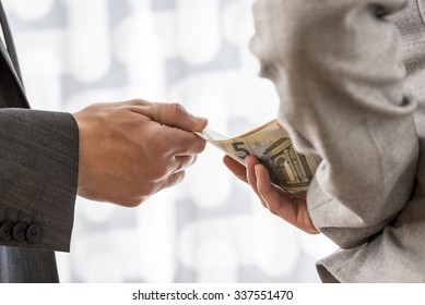 Businessman or politician taking bribe from a female colleague handing him Euro money from behind her back. Conceptual of corruption and bribery.