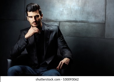 Businessman Portrait. Confident serious businessman sitting in armchair, looking at camera.