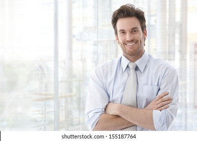 Businessman portrait. Happy confident young businessman standing arms crossed, smiling, looking at camera.
