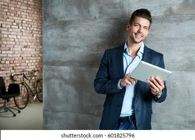 Businessman portrait. Happy businessman using tablet at office.