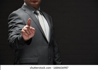 GeschäftsmännPortrait mit Zeigefinger, gekleidet in grauem Anzug, dunkler Hintergrund