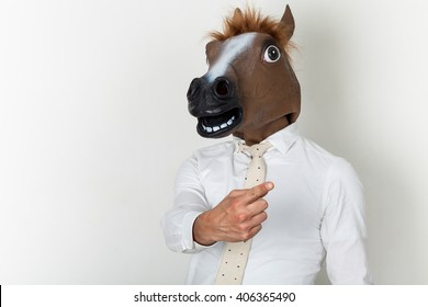 Businessman portrait wearing horse head and finger-pointing
