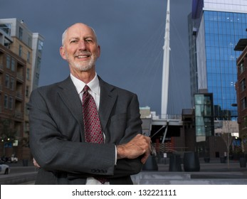 Businessman posing to the camera on plaza in the urban area.