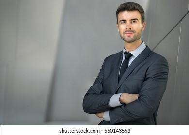 Businessman posing confident and positive in professional workplace office with space