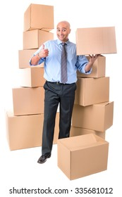 Businessman posing near a stack of cardboard boxes