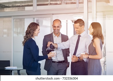 Businessman pouring coffee for collegues in a meeting room. Businessmen and businesswomen take coffee break after conference. Happy formal business team drinking coffee and relaxing at work.