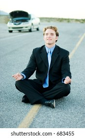 Businessman practices meditation while waiting for help
