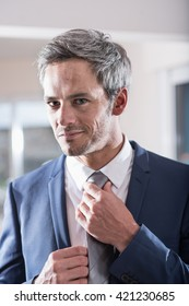 businessman preparing to go to an important appointment, he is looking at the mirror adjusting his tie