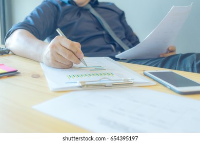 A businessman is preparing to summarize data for the annual report. Concept business and financial in cool tone.