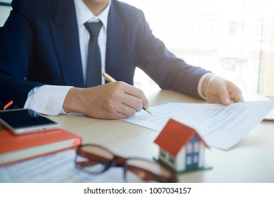 Businessman present contact of house insurance contract to purchase a home with a real estate agent.