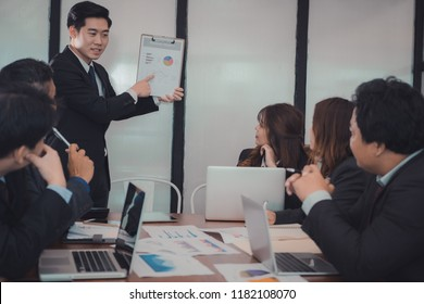 businessman present financial plan report to co worker team. man leader discuss sales data with investor colleagues. finance investment business meeting at office