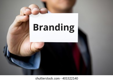 Businessman presenting 'Branding' word on white card