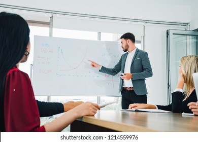 Businessman presenting to colleagues at a meeting.Successful team leader and business owner leading informal in-house business meeting. Businessman working on laptop in foreground.
