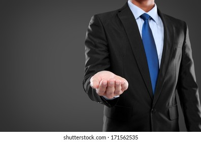 Businessman presenting copyspace against dark background