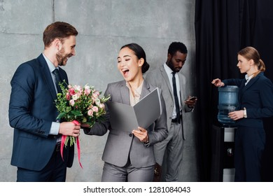 businessman presenting flowers to cheerful asian businesswoman with colleagues on background in waiting hall
