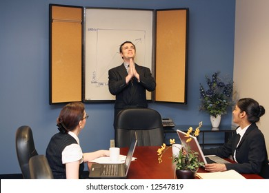 Businessman presenting to his colleagues staring up at the ceiling with his hands joined in prayer