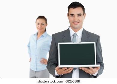 Businessman presenting laptop with businesswoman in the background against a white background