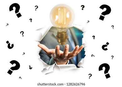 businessman presenting a lightbulb as the best idea breaking through a paper wall with many questionmarks on it