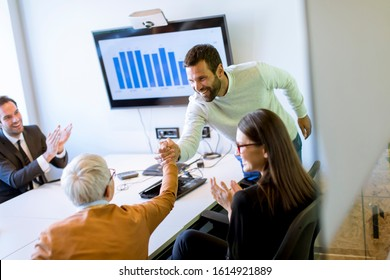 Businessman presenting project strategy showing ideas on interactive whiteboard in office - Shutterstock ID 1614921889