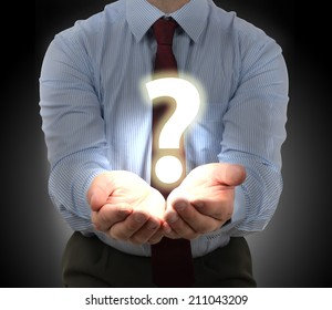 Businessman presenting a question mark glowing over hands
