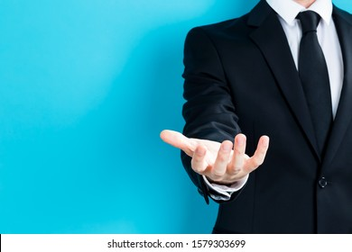 Businessman presenting something in his hand on a blue background