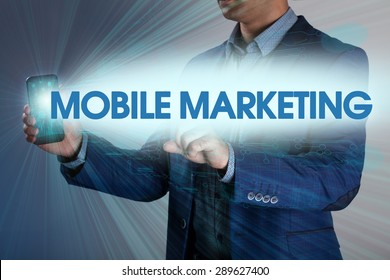 Businessman presses button mobile marketing on virtual screens. Business, technology, internet and networking concept.