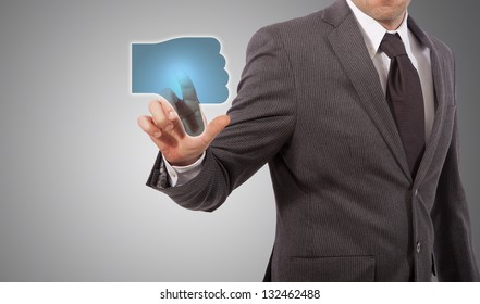 Businessman Presses a dislike Button, grey background