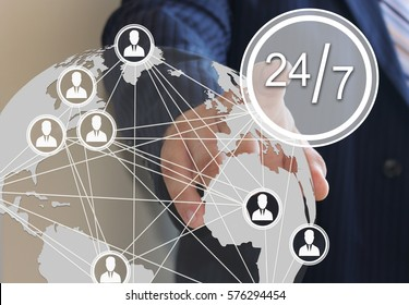 Businessman pressing 24 hours 7 days web service icon on a virtual screen. The concept of support 365 days a year, 7 days a week, 24 hours a day.