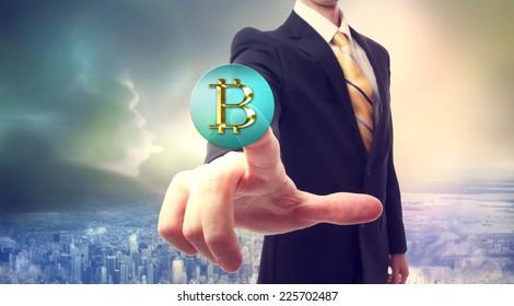 Businessman pressing a Bitcoin button over big city background