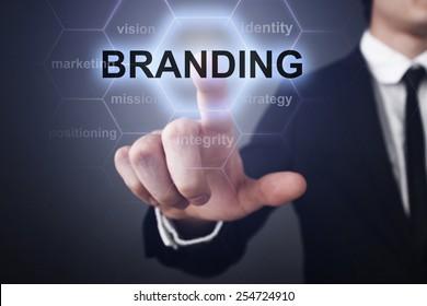 businessman pressing branding button on virtual screens. business concept