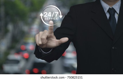 Businessman pressing button 24 hours service icon over blur of rush hour with cars and road, Full time service concept