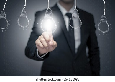 businessman pressing button with bulb on virtual screen