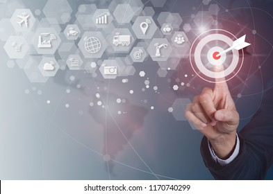 Businessman pressing button goal on virtual screen and Internet of things (IOT) word and objects icon connecting together, Internet networking concept, Connect global wireless devices with each other.