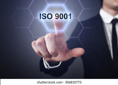 """Businessman pressing button on touch screen interface and select """"ISO 9001"""". Business concept. Internet concept."""
