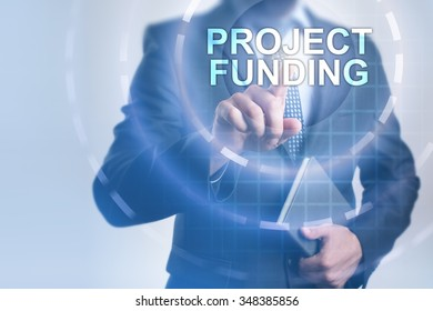 Businessman pressing button on touch screen interface and select Project funding. Business, internet, technology concept.