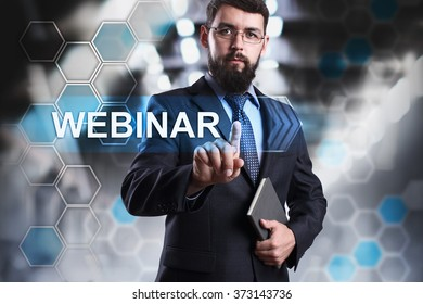 """Businessman pressing button on touch screen interface and selecting """"Webinar"""". Business, internet and tehcnology concept."""
