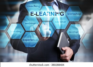 "Businessman pressing button on touch screen interface and select ""E-learning"". Business concept. Education concept."