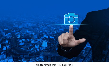 Businessman pressing camera flat icon over modern city tower, street and expressway, Business camera service concept