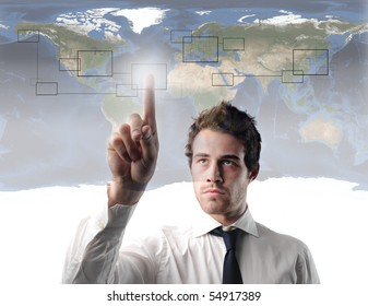 Businessman pressing the cell of a digital graphic with world map on the background