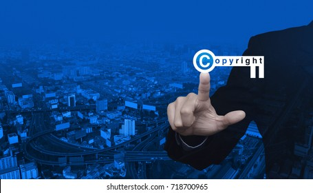 Businessman pressing copyright key icon over modern city tower, street and expressway, Copyright and patents concept
