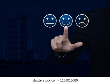 Businessman pressing excellent smiley face rating icon over world map and modern city tower, Business customer service evaluation and feedback rating concept, Elements of this image furnished by NASA