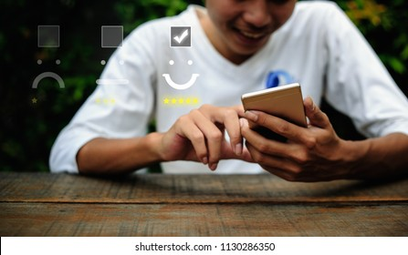 Businessman pressing face emoticon on virtual touch screen at smartphone .Customer service evaluation concept.