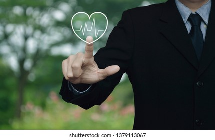 Businessman pressing heart beat pulse flat icon over blur flower and tree in park, Business medical health care service concept