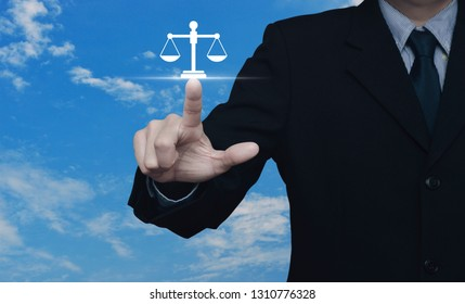Businessman pressing law flat icon over blue sky with white clouds, Business legal service concept