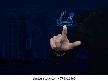 Businessman pressing motor bike icon over world map and modern city tower, Business delivery service concept, Elements of this image furnished by NASA