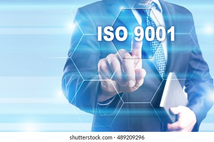 """Businessman is pressing on the virtual screen and selecting """"ISO 9001""""."""