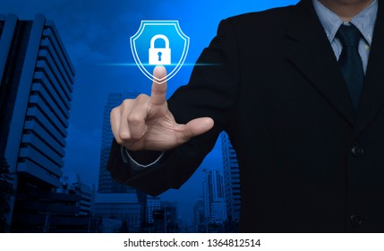 Businessman pressing padlock with shield flat icon over modern office city tower and skyscraper, Business security insurance concept