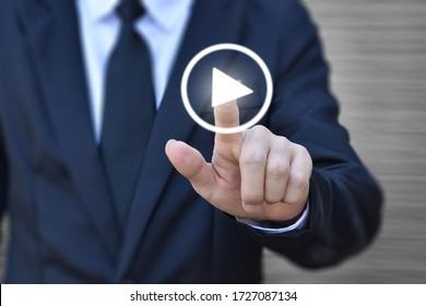 Businessman pressing play button to start. Idea for business, technology, and presentation.