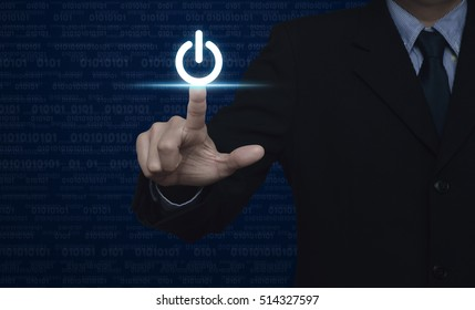 Businessman pressing power button over computer binary code blue background