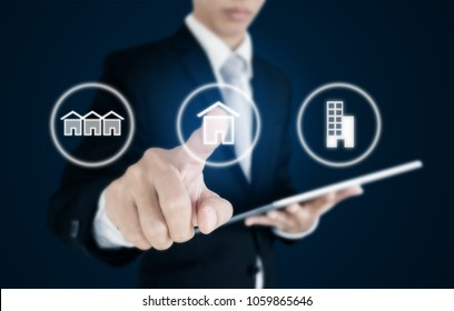 Businessman pressing real estate icons on screen. Business investment in real estate, town house, single home and condominium